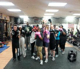 Boxing, Kickboxing class with trainer, doing heavy bag drill and punching technique