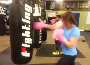 Heavy bag punch combos in boxing class with personal trainer in Nanuet gym
